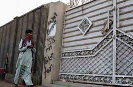 FILE - A man looks at graffiti supporting the Islamic State group as he walks past an entrance of a compound in Karachi, Pakistan, Nov. 12, 2014. Pakistani officials deny that IS has a foothold in the country.