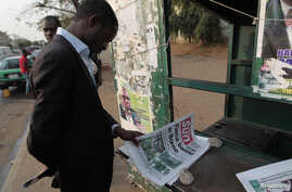 A man looks at a newspaper at a news stand in Abuja, Jan. 26, 2015.