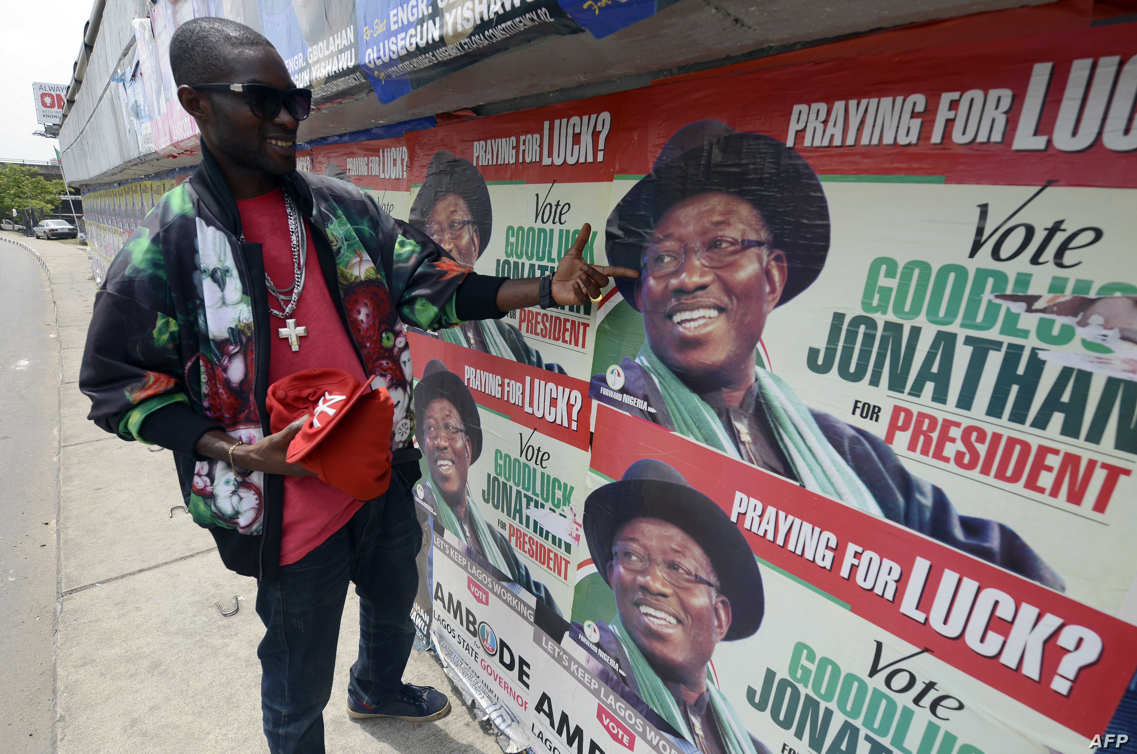 A man points to campaign posters of Nigerian President Goodluck Jonathan and candidate of the ruling People's Democratic Party (PDP) in Lagos, March 21, 2015.