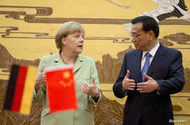 German Chancellor Angela Merkel (L) chats with Chinese Premier Li Keqiang during the signing ceremony at the Great Hall of the People in Beijing, July 7, 2014.