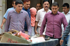 Indian policemen escort the juvenile (C, in pink hood), accused in the December 2012 gang-rape of a student, following his guilty verdict at a court in New Delhi, Aug. 31, 2013.
