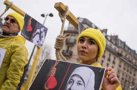 FILE - A demonstrator poses with a symbolic rope around her neck as Iranian opposition protesters march during a rally to protest against executions in Paris, France.