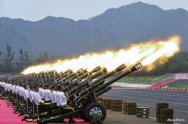 FILE - Paramilitary policemen and members of a gun salute team fire cannons during a training session for a military parade to mark the 70th anniversary of the end of the World War Two, at a military base in Beijing, China.