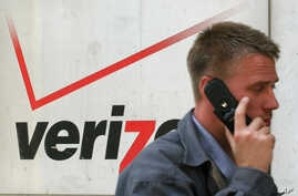 A cell phone user passes a Verizon store in this Thursday April 27, 2006 file photo in New York.