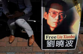 A protester displays a portrait of jailed Chinese Nobel Peace laureate Liu Xiaobo during a demonstration outside the Chinese liaison office in Hong Kong, July 11, 2017.