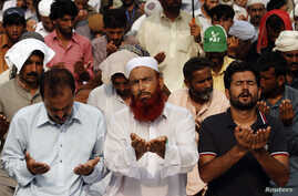 Supporters of Tahir ul-Qadri, Sufi cleric and leader of political party Pakistan Awami Tehreek, offer prayers in front of the Parliament House during the Revolution March in Islamabad, Aug. 22, 2014.