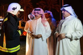 In this photo released by Bahrain News Agency, Sheikh Rashid bin Abdullah Al Khalifa, Bahrain Minister of Interior talks with a member of the emergency services, during his visit to the scene of an explosion, in Bahrain, Saturday, Nov. 11, 2017.  Bah