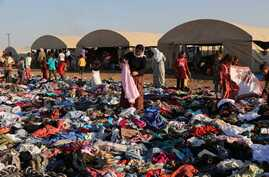 FILE - Displaced Iraqis from the Yazidi community look for clothes to wear among items provided by a charity organization at the Nowruz camp, in Derike, Syria, Aug. 12, 2014.