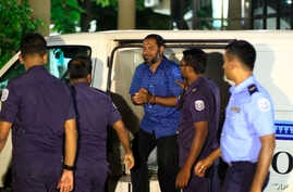 Sheik Imran Abdulla, leader of the Islamic conservative Adhaalath, or Justice Party, is escorted to court in Male, Maldives, May 2, 2015.