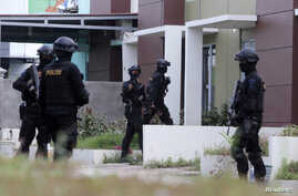 FILE - Indonesian anti-terror police from Detachment 88 are seen entering a building during a raid in Batam, Riau Islands, Indonesia.