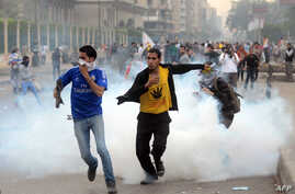 Supporters of ousted president Mohamed Morsi and the Muslim brotherhood run away from tear gas during clashes with Egyptian riot police close to Rabaa al-Adawiya square, Nov. 22, 2013.