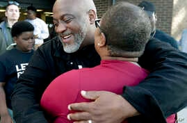 Former felon Desmond Meade and president of the Florida Rights Restoration Coalition, left, hugs Melanie Campbell with the National Coalition Black Civic Participation, after registering to vote on Jan. 8, 2019, in Orlando, Fla.