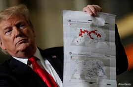 """President Donald Trump shows maps of Syria and Iraq depicting the size of the """"ISIS physical caliphate"""" as he speaks to workers while touring the Lima Army Tank Plant Joint Systems Manufacturing Center, the country's only remaining tank manufacturing"""