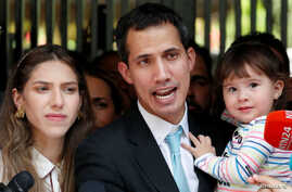 Venezuelan opposition leader and self-proclaimed interim president Juan Guaido talks to media next to his wife Fabiana Rosales, while carrying their daughter outside their home after a meeting with supporters to present a government plan of the oppos