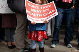 A girl stands holding a sign alongside supporters of the Affordable Care Act who are also opponents of Colorado's GOP-led plan to undo Colorado's state-run insurance exchange at a rally on the state Capitol steps in Denver, Jan. 31, 2017.