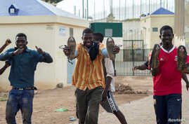 FILE - African migrants react as they arrive at the short-stay immigrant center after crossing the border from Morocco to Spain's North African enclave of Melilla, Spain, June 26, 2016.