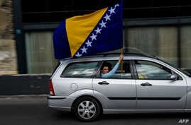 A man waves the Bosnian flag in Sarajevo, Oct. 6, 2018, on the eve of Bosnian tripartite presidency election. Bosnians head to the polls Sunday to elect leaders who will steer the poor nation shackled by the communal divides that fueled its brutal wa