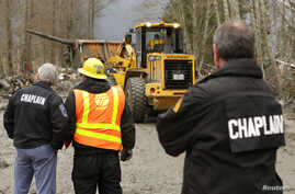 Washington State Police chaplains watch as workers dig through debris left following a mudslide, near Oso, Washington, March 25, 2014.