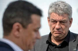 FILE - Eeconomy minister Mihai Tudose (R) looks at former prime minister Sorin Grindeanu in Caravelle, Romania, May 12, 2017.