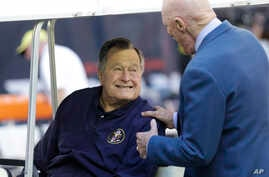FILE - Former President George H.W. Bush  talks with Houston Texans owner Bob McNair before a National Football League game between the Texans and the Cincinnati Bengals in Houston, Nov. 23, 2014.