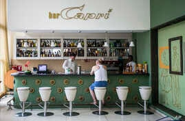 FILE - In this Sept. 12, 2017, file photo, a customer sits at the lobby bar of the Hotel Capri in Havana, Cuba. Doctors are releasing the first detailed medical reports about the hearing, vision, balance and brain symptoms suffered in what the State