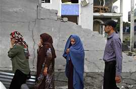 Afghans walk through the site of an attack on an international compound in Kabul, Afghanistan