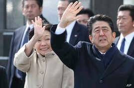 FILE - Japan's Prime Minister Shinzo Abe and his wife, Akie Abe, wave as the emperor and empress depart for Vietnam, Feb. 28, 2017. Akie Abe denies making a donation to a school at the heart of a political scandal.