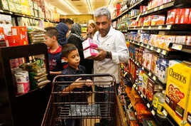 Nadim Fawzi Jouriyeh, a Syrian refugee who arrived recently in the United States with his wife and four children, puts items in a cart while shopping with his son, Farouq Nadim Jouriyeh, in El Cajon, Calif., Aug. 31, 2016.