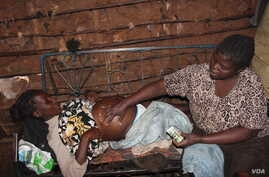 Mama Atoti massaging a pregnant woman belly, using Arimis - a popular petroleum jelly commonly used by farmers to apply on their hands before milking cows, Nairobi, June 18, 2016. (R. Ombour/VOA)