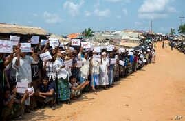 Rohingya refugees holding placards await the arrival of a U.N. Security Council team at the Kutupalong Rohingya refugee camp in Kutupalong, Bangladesh, April 29, 2018. A U.N. Security Council team visiting Bangladesh promised Sunday to work hard to r...