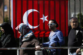 People wait outside the Turkish consulate in Berlin, March 27, 2017 to cast their votes on the first day of the referendum on the presidential system in Turkey.
