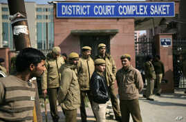 Delhi policemen stand guard near the gate of a district court where the accused in the gang rape and murder of a 23-year-old student are undergoing trial, in New Delhi, India, Jan. 24, 2013.