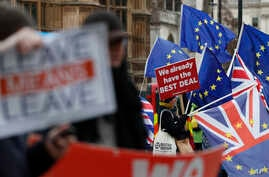Pro and anti Brexit demonstrators wave their placards and flags outside the Houses of Parliament in London, Dec. 18, 2018.