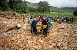 Men carry a coffin on along a makeshift path on the river in Ngangu township Chimanimani, Manicaland Province, eastern Zimbabwe, after the area was hit by the cyclone Idai.
