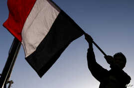A Yemeni waves a national flag during a rally celebrating the death of Yemeni ex-president Ali Abdullah Saleh a day after he was killed, in the capital Sana'a, Dec. 5, 2017.