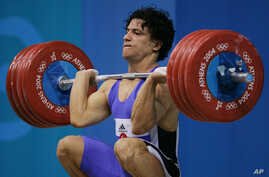 FILE - Shahin Nasirinia of Iran lifts in the clean and jerk during the men's 207 lb  (94 kg) event at the Nikaia Olympic Weightlifting Hall during the Summer Olympics in Athens, Monday Aug. 23, 2004.