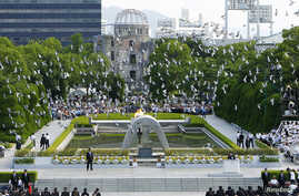 Doves fly over the Peace Memorial Park with a view of the gutted A-bomb dome at a ceremony in Hiroshima, Japan, Aug. 6, 2010.