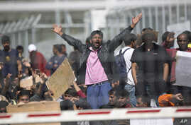 Refugees and migrants most of them from Pakistan protest against EU-Turkey deal about migration inside the entrance of Moria camp in the Greek island of Lesbos on April 5, 2016.