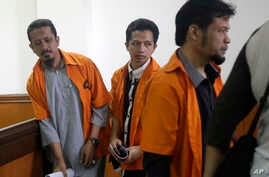 FILE - Suspected militants Abdul Hakim (from left), Ahmad Junaedi and Tuah Febriwansyah attend trial at West Jakarta District Court in Jakarta, Indonesia, Oct. 12, 2015.