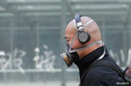A man wearing a mask is seen on a street in Beijing May 2,  2013.  Street-level anger over air pollution that blanketed many northern cities this winter spilled over into online appeals for Beijing to clean water supplies, especially after rotting co