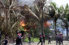 Policemen walk towards burning buildings in Sittwe, capital of Rakhine state in western Burma, where sectarian violence is ongoing, June 12, 2012.