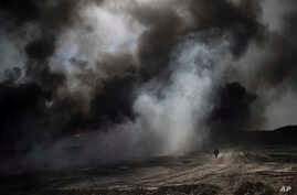 An oil worker walks next to burning oil fields in Qayara, south of Mosul, Iraq, Tuesday, Nov. 22, 2016. For months, residents of the Iraqi town of Qayara have lived in the darkness from a cloud of toxic fumes released by oil fields lit by retreating