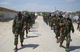 Members of Somalia's al- Shabab militant group patrol on foot on the outskirts of Mogadishu, March, 5, 2012.