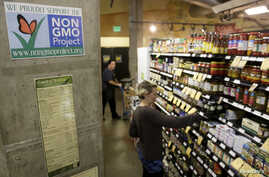 FILE - Employees stock shelves near a sign supporting non genetically modified food at the Central Co-op in Seattle, Washington October 29, 2013.