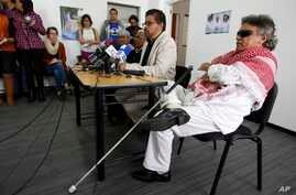 Ivan Marquez, chief negotiator of the Revolutionary Armed Forces of Colombia, second from right, talks to reporters as Jesus Santrich, right, Victoria Sandino, left, and Joaquin Gomez, second left, listen in Bogota, Colombia, Dec. 6, 2016. Marquez ha