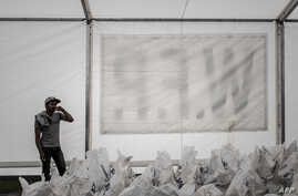 FILE - A worker stands by bags of rice stored under a tent of the World Food Programme (WFP) in Deurali village of Nepal's Gorkha district, May 6, 2015.