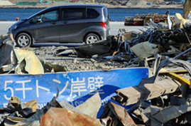 A car passes in front of tsunami debris piled up on the wh