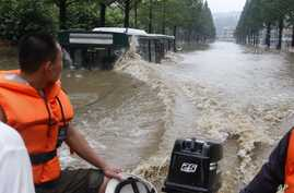 A boat goes pass a flooded street in Anju City, South Phyongan Province, in North Korea, July 30, 2012.