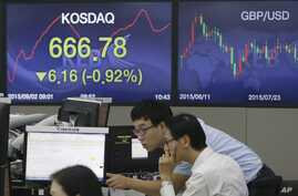 Currency traders work at the foreign exchange dealing room of the KEB Hana Bank headquarters in Seoul, South Korea, Wednesday, Sept. 2, 2015.