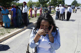 A woman reacts with others as they await word on a shooting at a Sikh temple in Oak Creek, Wis., Sunday, Aug. 5, 2012, where police and witnesses describe a chaotic situation with an unknown number of victims, suspects and possible hostages.